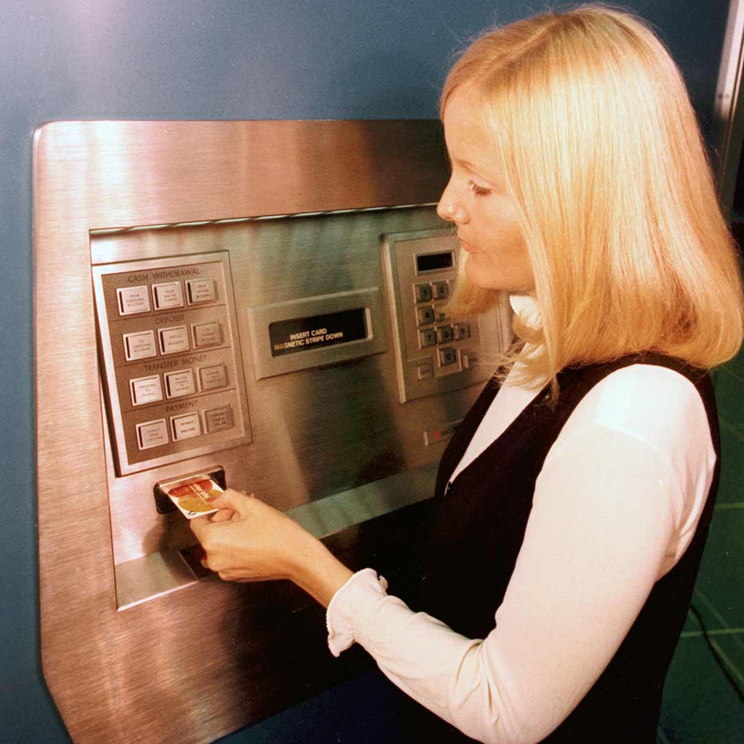 Archival image of a woman withdrawing cash from an old ATM